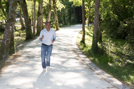 un hombre casual indio correr en un parque con jeans