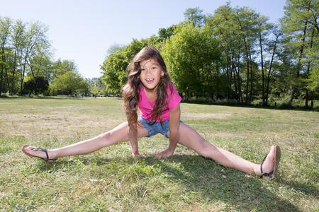 女の子子供が遊ぶ公園で体操を行う 写真素材
