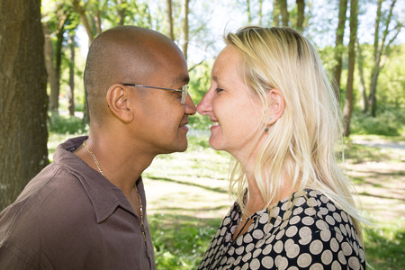 mixed couple makes a nose against a nose outside Stock Photo