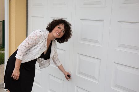 Vrouw met gekruld haar open de garage deuren
