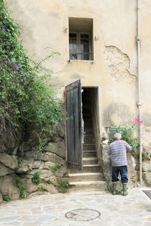 wood texture: An old person seen from behind with a cane entering his old medieval house