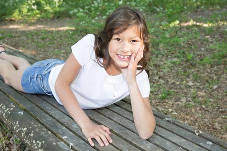 Jovem menina de 10 anos deitado no jardim do banco Foto de archivo - 78879439