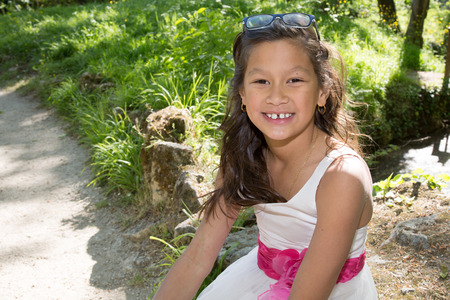 young 10 year old girl sitting in a park Stock Photo