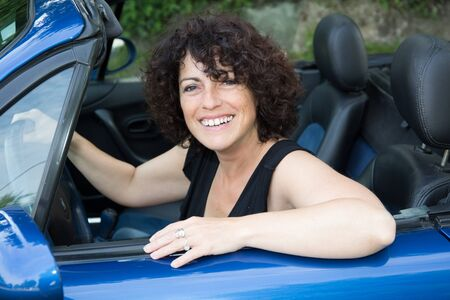 forties: woman with curly hair sitting in a convertible car
