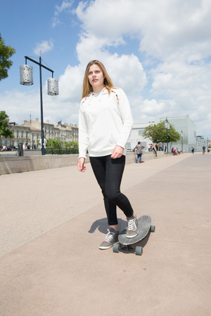 pretty blond teenager in city Bordeaux in France with skateboard