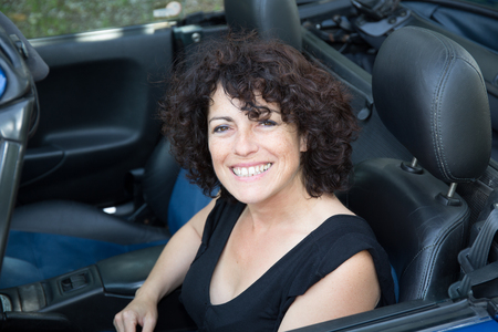 smiling happy curly haired woman in her convertible car