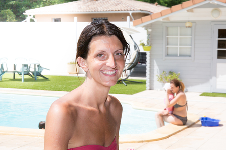 beautiful woman smiling with her hair tied to the pool with her friends Stock Photo