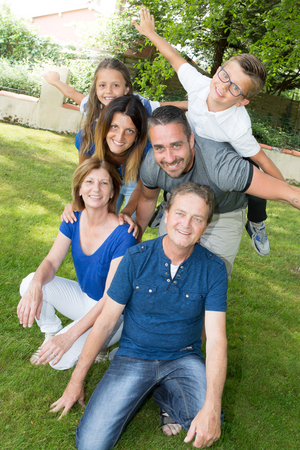 family of 6 with grandchildren parents and grandparents in fun Stock Photo