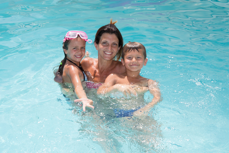 pretty young family with mother and two children in pool