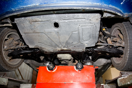 to mend: Car on lift in the auto shop  reveals an exhaust with gasoline pipe lifted