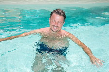 handsome and happy mid aged man relaxing at the side of a sun bathed swimming pool smiling Stock Photo