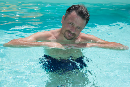 forties man in pool summer family Stock Photo