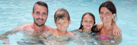 若い 4 人家族のプールで水浴びを楽しむ