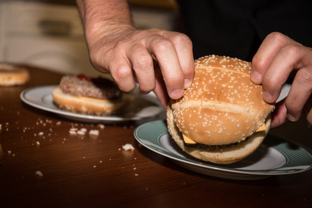 Male cook is preparing burgers on a table Stock Photo