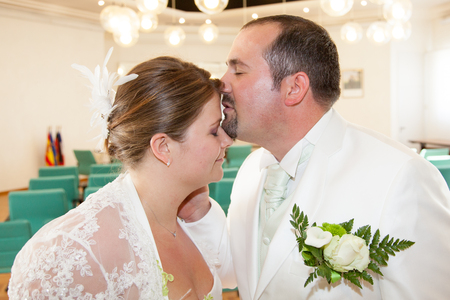 Blond bride kisses a groom in a city hall Stock Photo