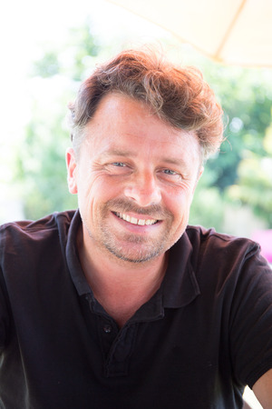 Portrait shot of an attractive, successful and happy middle aged man male outside