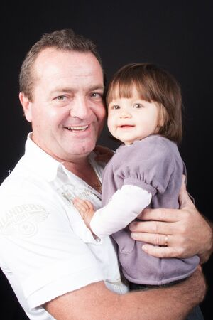 彼の腕の中で小さな孫娘を持って幸せの祖父 写真素材