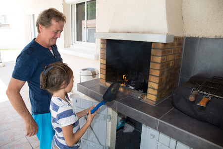 grandfather makes a barbecue with his granddaughter Stock fotó