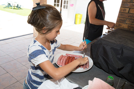 young girl participates in the preparation of the bbq by piercing the sausages Stock fotó