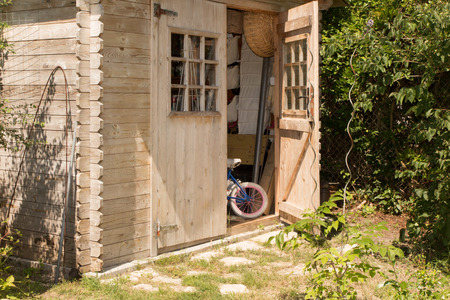 Jardin avec outils de jardinage et cabanon en bois Banque d'images - 84725644