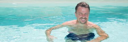 Handsome middle aged man in sunny swimming pool on vacation