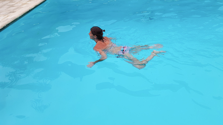 Portrait of beautiful tanned woman in swimwear relaxing in swimming pool Stock Photo