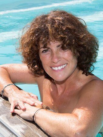 Upper view of cute woman relaxing in resort pool