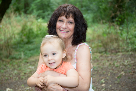 grandmother with granddaughter in knees in summer park Stock Photo
