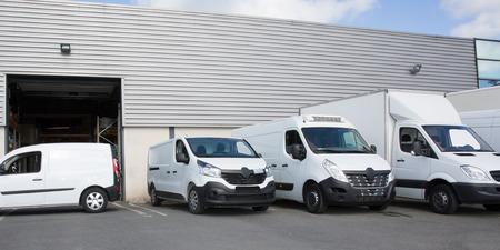 Verschillende auto's, bestelwagens en vrachtwagens geparkeerd op de parkeerplaats, klaar voor verhuur of verkoop