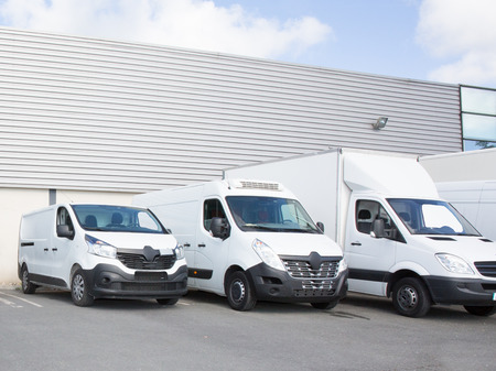 specialized delivery society parking with small trucks and van Archivio Fotografico
