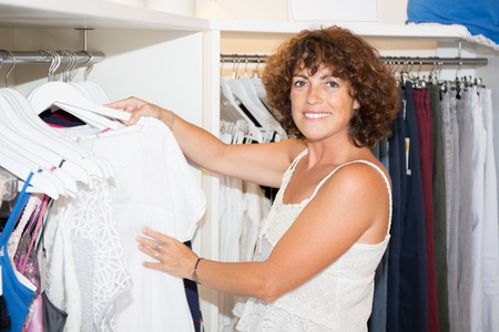 forties woman shopping in clothing store Фото со стока