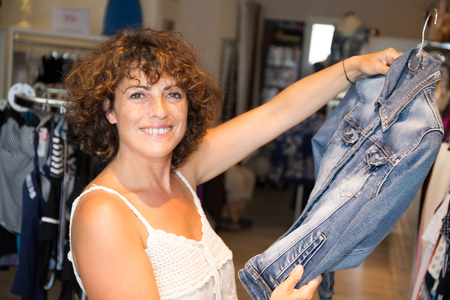 Woman choosing a dress in clothing shop