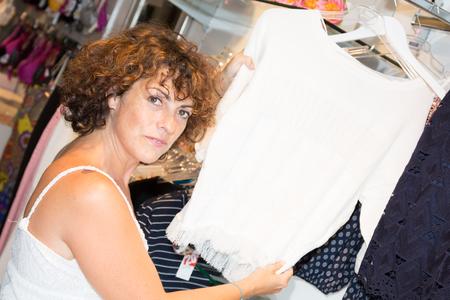 Woman is choosing a dress in clothing shop