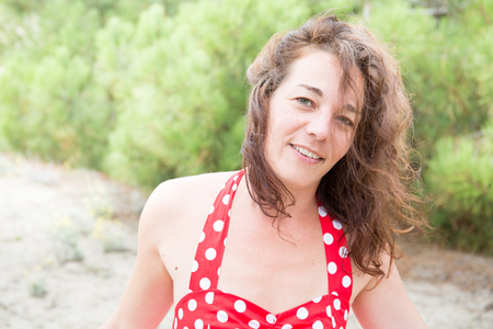 portrait of woman in red swim suit relaxing on beach