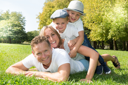 is green: Happy beautiful young family lying on the green grass. four cheerful person Stock Photo
