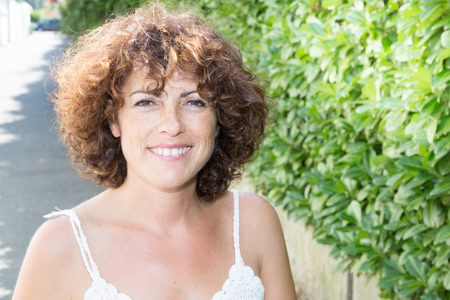 is green: Portrait of beautiful real 40 years old woman in the park Stock Photo