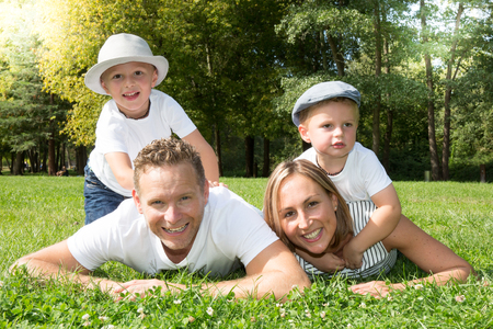 is green: family lifestyle portrait of a mum and dad with sons having good time on the green grass Stock Photo