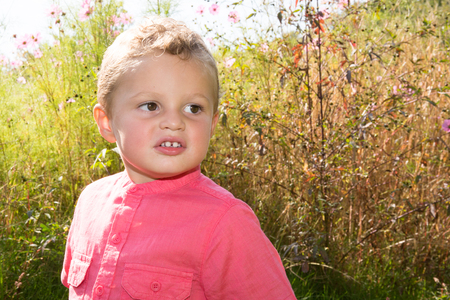 is green: A close-up cute little blonde two years old boy outdoors against a blurred green background