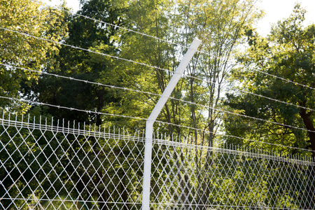 Line of barbed wire fence around prison walls Stock Photo