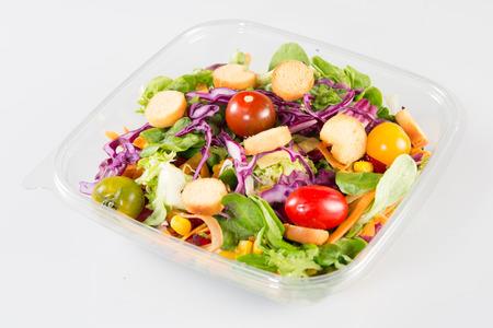 ensalada de verduras en la taza de plástico clara