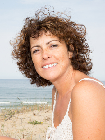 happy woman on the sand near sea, summer time Stock Photo