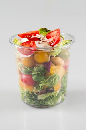 白い背景で隔離のプラスチック容器のドレッシング サラダ 写真素材