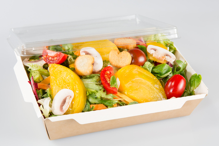 packed salads in takeaway container on white background