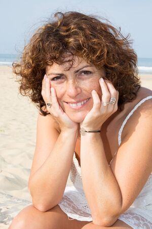 Happy woman on the beach. Portrait of the beautiful girl close-up