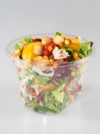 Salad in takeaway container on white background