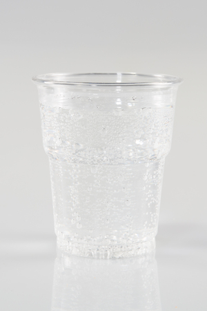 plastic cup glass of water with bubbles on white background
