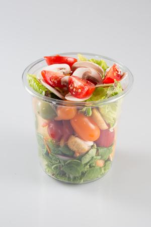 Envases frescos transparentes de plástico con ensalada en una mesa de cristal