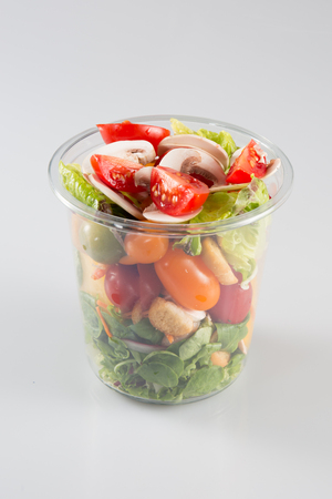 Plastic transparent fresh containers with salad on a glass table