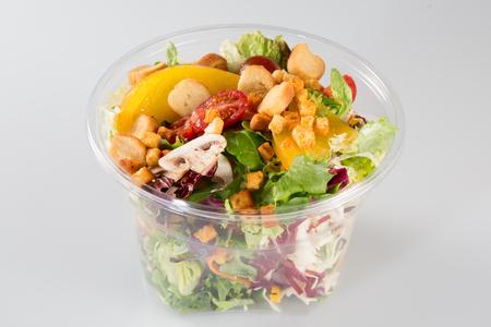 Envase de la taza de ensalada fresca sobre fondo blanco Foto de archivo