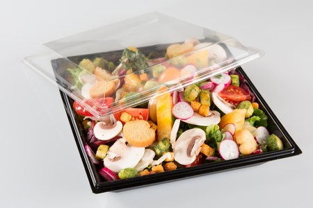 traditional salad in a black plastic container isolated on a white background